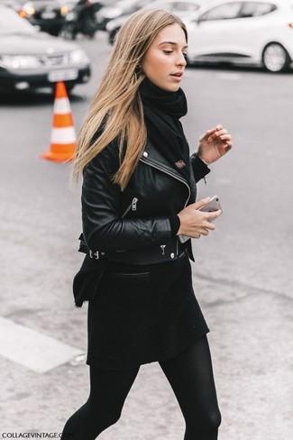 Cómo combinar: bufanda negra, minifalda de lana negra, jersey con cuello circular negro, chaqueta motera de cuero negra