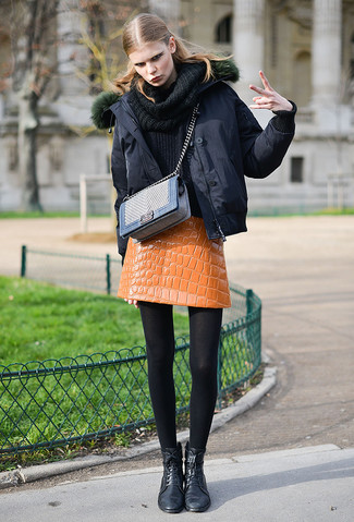 Cómo combinar: botas planas con cordones de cuero negras, minifalda de cuero naranja, jersey con cuello vuelto holgado negro, plumífero negro