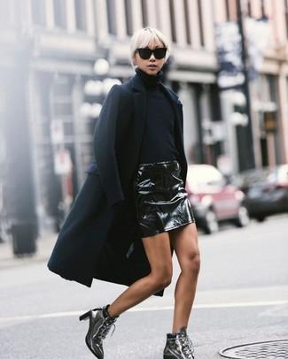 Cómo combinar: botines con cordones de cuero plateados, minifalda de cuero negra, jersey de cuello alto negro, abrigo negro