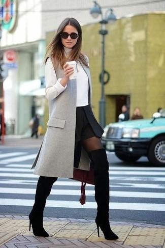 Cómo combinar: botas sobre la rodilla de ante negras, minifalda negra, jersey de cuello alto blanco, abrigo sin mangas gris