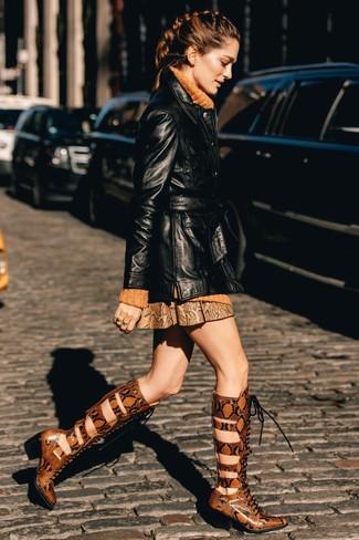 Combinar una gabardina de cuero negra: Equípate una gabardina de cuero negra con una minifalda de cuero con print de serpiente marrón para una vestimenta cómoda que queda muy bien junta. Completa el look con botas de caña alta de cuero con print de serpiente en tabaco.