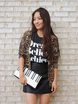 Cómo combinar: cartera sobre de cuero estampada en blanco y negro, minifalda de cuero negra, camiseta con cuello circular estampada en negro y blanco, cárdigan abierto de leopardo marrón claro