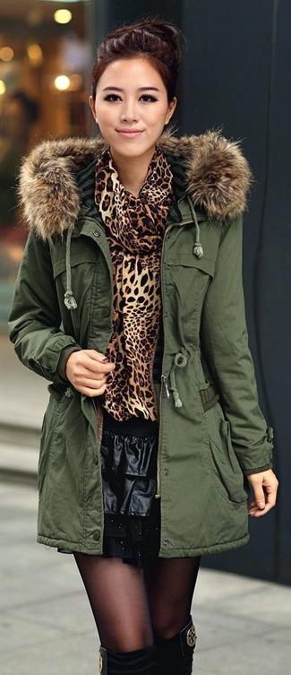 Cómo combinar: medias negras, minifalda de cuero plisada negra, jersey con cuello vuelto holgado de leopardo marrón, parka verde oscuro