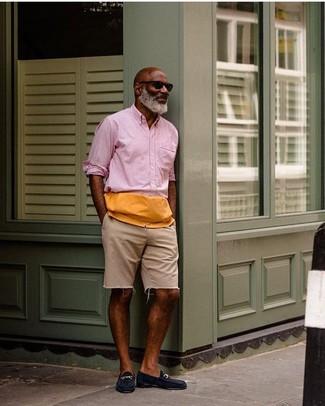 Cómo combinar: gafas de sol negras, mocasín de ante azul marino, pantalones cortos vaqueros en beige, camisa de manga larga rosada