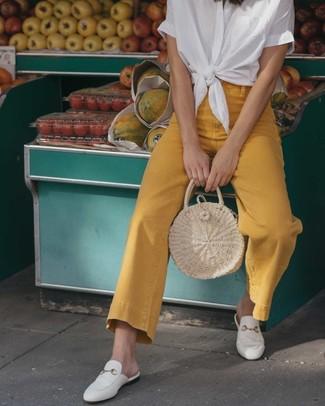 Cómo combinar: bolsa tote de paja en beige, mocasín de cuero blancos, vaqueros de campana mostaza, camisa de manga corta blanca