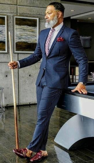 Combinar una corbata de tartán en rojo y azul marino: Usa un traje de rayas verticales azul marino y una corbata de tartán en rojo y azul marino para rebosar clase y sofisticación. ¿Quieres elegir un zapato informal? Haz mocasín de cuero burdeos tu calzado para el día.