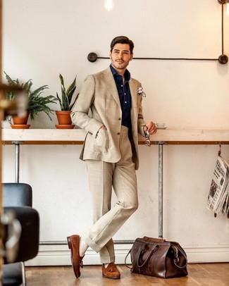 Cómo combinar: bolsa de viaje de cuero en marrón oscuro, mocasín con borlas de ante en tabaco, camisa de manga larga de cambray azul marino, traje en beige