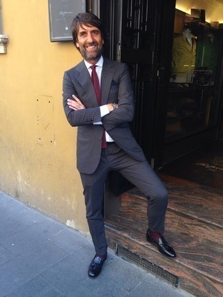 Combinar un traje de rayas verticales en gris oscuro: Equípate un traje de rayas verticales en gris oscuro junto a una camisa de vestir blanca para una apariencia clásica y elegante. Mocasín con borlas de cuero negro son una opción estupenda para complementar tu atuendo.