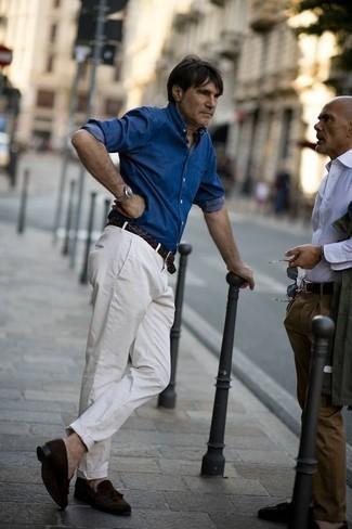 Outfits hombres estilo casual elegante: Considera ponerse una camisa vaquera azul y un pantalón chino blanco para una vestimenta cómoda que queda muy bien junta. Opta por un par de mocasín con borlas de ante en marrón oscuro para mostrar tu inteligencia sartorial.