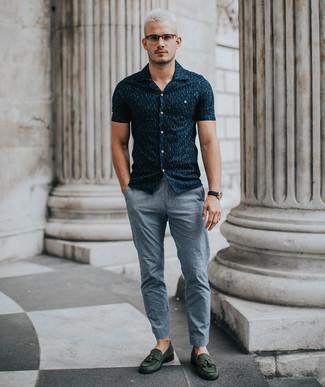 Cómo combinar: reloj de cuero negro, mocasín con borlas de ante verde oscuro, pantalón chino gris, camisa de manga corta estampada azul marino