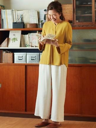 Cómo combinar: mocasín de cuero marrónes, pantalones anchos blancos, blusa de manga larga mostaza