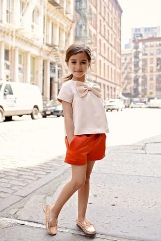 Cómo combinar: mocasín dorados, pantalones cortos naranjas