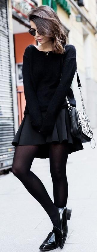Cómo combinar: bolso bandolera de cuero con print de serpiente negro, mocasín de cuero negros, falda skater negra, jersey oversized negro