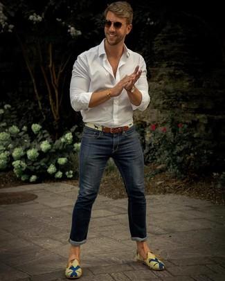 Cómo combinar: correa de lona en beige, mocasín de lona estampado en multicolor, vaqueros pitillo azul marino, camisa de manga larga blanca