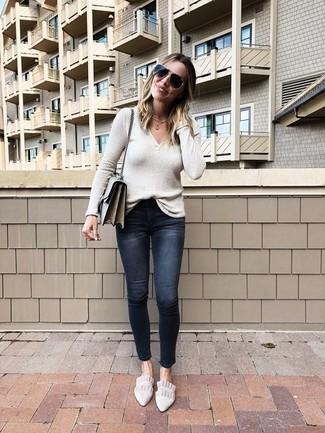 Cómo combinar: bolso bandolera de cuero gris, mocasín de ante en beige, vaqueros pitillo desgastados negros, jersey de pico en beige