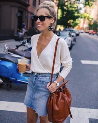 Cómo combinar: gafas de sol negras, mochila de cuero en tabaco, minifalda vaquera azul, jersey de pico en beige