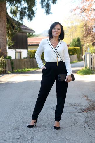 Cómo combinar: mono en blanco y negro, zapatos de tacón de ante negros, cartera sobre de cuero con print de serpiente negra, colgante dorado