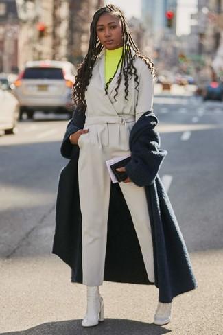 Cómo combinar: botines de cuero blancos, mono gris, jersey de cuello alto amarillo, abrigo de angora azul marino