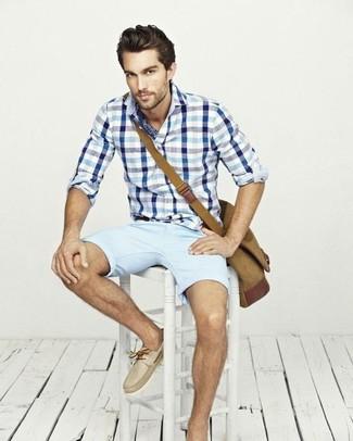 Cómo combinar: bolso mensajero de lona marrón claro, náuticos de cuero en beige, pantalones cortos celestes, camisa de manga larga de cuadro vichy en blanco y azul