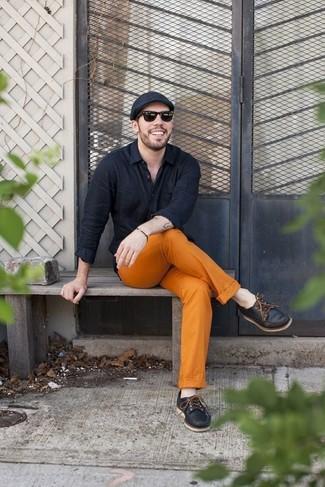 Cómo combinar: gorra inglesa negra, náuticos de cuero negros, pantalón chino naranja, camisa de manga larga negra