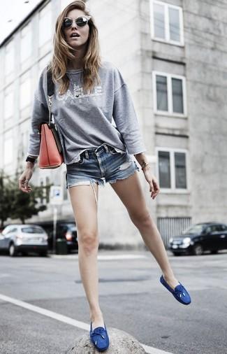 Cómo combinar: bolso bandolera de cuero rojo, náuticos de lona azul marino, pantalones cortos vaqueros azules, sudadera estampada gris