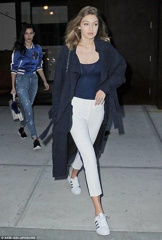 Cómo combinar: tenis de cuero blancos, pantalón capri blanco, camiseta sin manga azul marino, abrigo azul marino