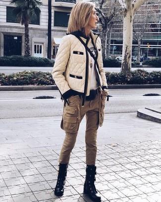 Cómo combinar: botas planas con cordones de cuero negras, pantalón cargo marrón, camiseta con cuello circular estampada en blanco y negro, cazadora de aviador acolchada en beige