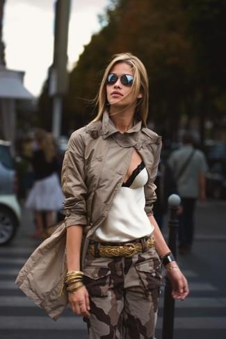 Cómo combinar: correa de cuero tejida dorada, pantalón cargo de camuflaje marrón, camiseta sin manga de encaje en blanco y negro, gabardina marrón