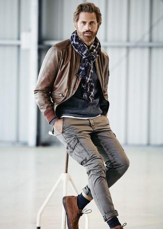Cómo combinar: botas safari de ante marrónes, pantalón cargo gris, jersey con cuello circular azul marino, cazadora de aviador de cuero marrón