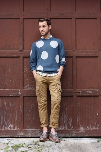 Cómo combinar: zapatos brogue de cuero en marrón oscuro, pantalón cargo marrón claro, camisa de manga larga estampada gris, jersey con cuello circular a lunares azul