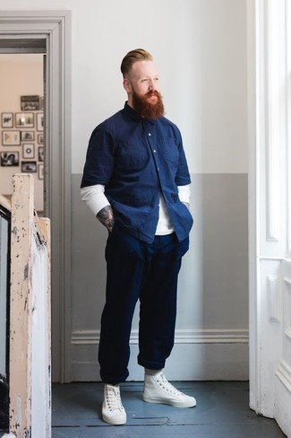 Cómo combinar: zapatillas altas de cuero blancas, pantalón chino azul marino, camisa de manga corta de cambray azul marino, jersey con cuello circular blanco