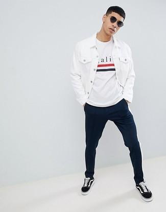 Cómo combinar: tenis de lona en negro y blanco, pantalón chino azul marino, camiseta con cuello circular estampada blanca, chaqueta vaquera blanca