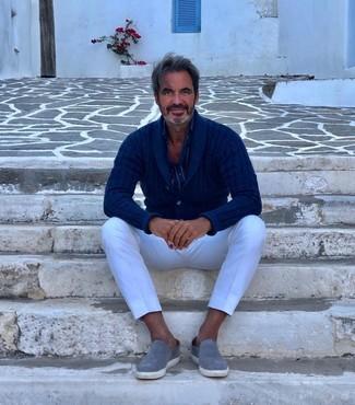 Cómo combinar: zapatillas slip-on de ante grises, pantalón chino blanco, camisa de manga larga de rayas verticales azul marino, cárdigan con cuello chal azul marino