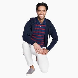 Cómo combinar: zapatillas slip-on de lona grises, pantalón chino blanco, camisa polo de rayas horizontales azul marino, sudadera con capucha azul marino