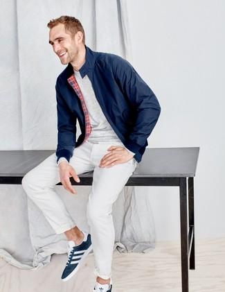 Cómo combinar: tenis de ante azul marino, pantalón chino blanco, camiseta de manga larga gris, cazadora harrington azul marino