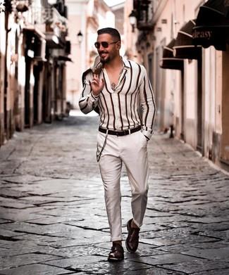 Cómo combinar: zapatos con doble hebilla de cuero en marrón oscuro, pantalón chino blanco, camisa de manga larga de rayas verticales blanca, blazer en beige