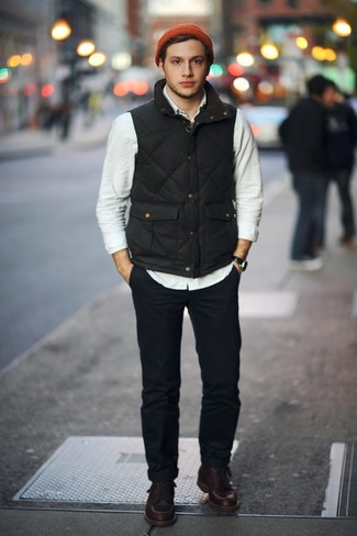 Cómo combinar: botas de trabajo de cuero en marrón oscuro, pantalón chino azul marino, camisa de manga larga en beige, chaleco de abrigo negro