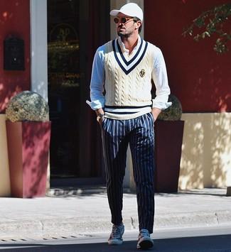 Cómo combinar: tenis de lona estampados blancos, pantalón chino de rayas verticales azul marino, camisa de manga larga celeste, chaleco de punto en beige