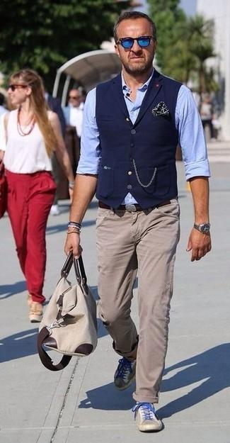Cómo combinar: tenis de ante en beige, pantalón chino en beige, camisa de manga larga de cambray celeste, chaleco de vestir azul marino