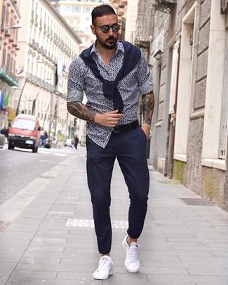 Cómo combinar: tenis de cuero blancos, pantalón chino azul marino, camisa de manga larga con print de flores en azul marino y blanco, jersey con cuello circular azul marino