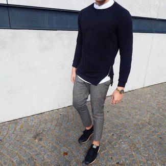 Cómo combinar: tenis de cuero negros, pantalón chino gris, camisa de manga larga blanca, jersey con cuello circular azul marino