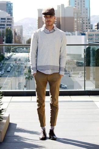 Cómo combinar: zapatos derby de cuero en marrón oscuro, pantalón chino marrón, camisa de manga larga gris, jersey con cuello circular gris