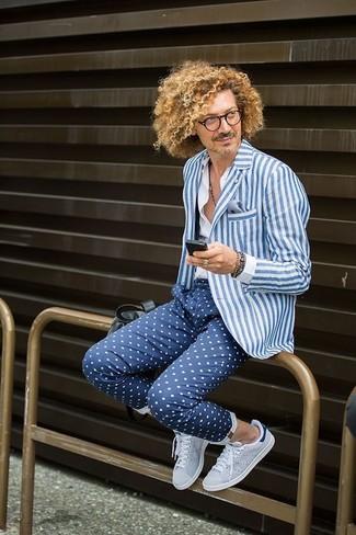Cómo combinar: tenis grises, pantalón chino a lunares azul marino, camisa de vestir blanca, blazer de rayas verticales en blanco y azul
