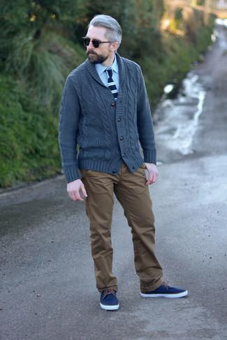 Moda para hombres de 40 años: Si buscas un estilo adecuado y a la moda, elige un cárdigan con cuello chal en gris oscuro y un pantalón chino marrón. ¿Quieres elegir un zapato informal? Haz tenis de lona azul marino tu calzado para el día.