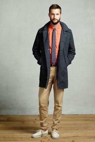 Cómo combinar: tenis de lona en beige, pantalón chino marrón claro, camisa de vestir naranja, gabardina negra