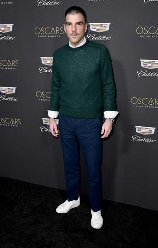 Cómo combinar: tenis blancos, pantalón chino azul marino, camisa de vestir blanca, jersey con cuello circular verde oscuro