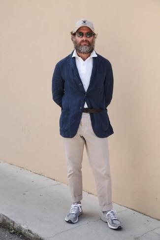 Combinar unas deportivas grises: Si buscas un estilo adecuado y a la moda, ponte un blazer de lino azul marino y un pantalón chino en beige. Si no quieres vestir totalmente formal, opta por un par de deportivas grises.
