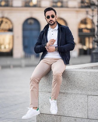 Look de moda: Tenis de cuero en blanco y verde, Pantalón chino a lunares en beige, Camisa polo blanca, Cazadora de aviador de ante azul marino