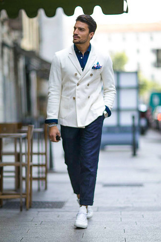 Cómo combinar: tenis blancos, pantalón chino azul marino, camisa vaquera azul marino, blazer cruzado blanco