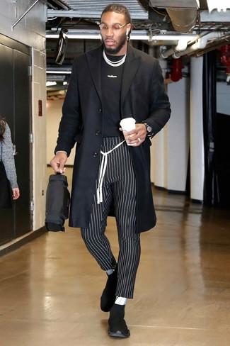 Cómo combinar: deportivas negras, pantalón chino de rayas verticales en negro y blanco, camiseta con cuello circular estampada en negro y blanco, abrigo largo negro